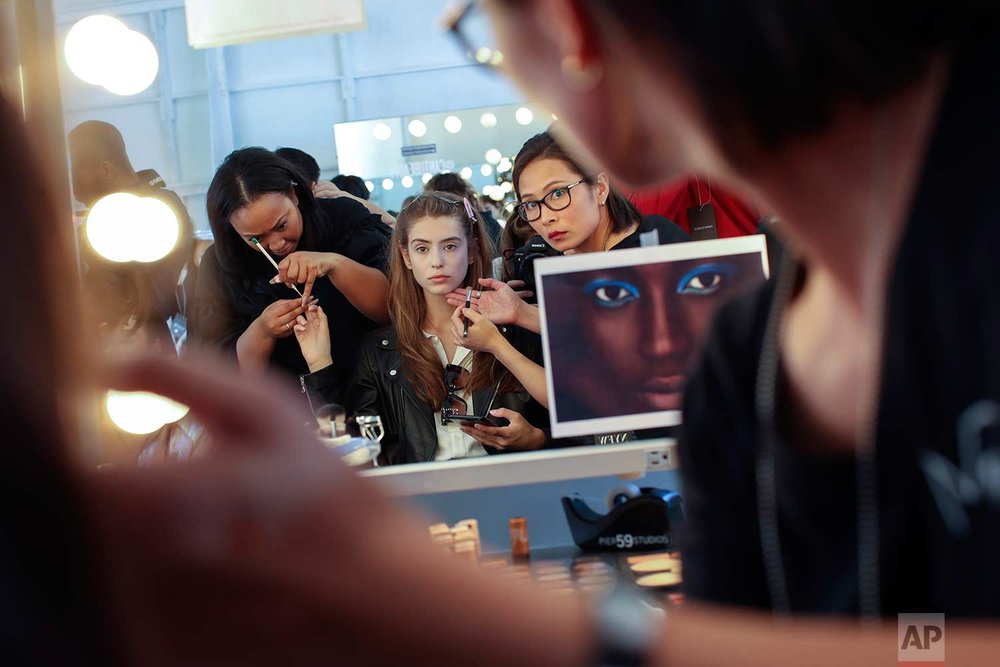 A model has her make up done backstage ahead of the Tracy Reese Spring 2018 presentation during New York Fashion Week, Sunday, Sept. 10, 2017. (AP Photo/Mary Altaffer)