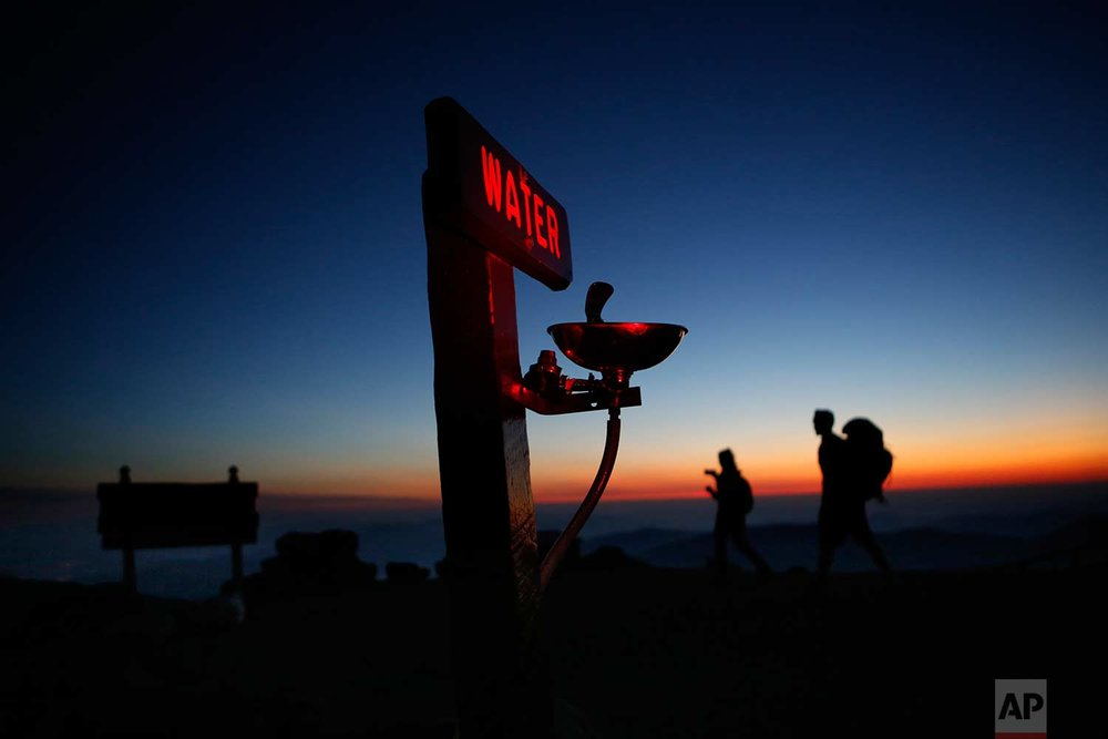 In this Sunday, Sept. 24, 2017 photo, Quincy Andrews, left, and Josh Fournier, both of Meredith, N.H., arrive at dawn at the summit of Mount Washington, N.H., where a water fountain awaits visitors to New England's highest peak. The weather observatory on the summit recorded a record daily temperature high Sunday when the mercury hit 65 degrees, the highest ever for a Sept. 24. (AP Photo/Robert F. Bukaty)