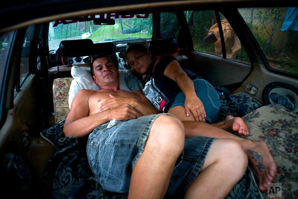 Blanca Rivera and Eduard Rodriguez sleep in their car to protect themselves from the elements, since their house was destroyed by Hurricane Maria, in the San Lorenzo neighborhood of Morovis, Puerto Rico, Saturday, Sept. 30, 2017. (AP Photo/Ramon Espinosa)