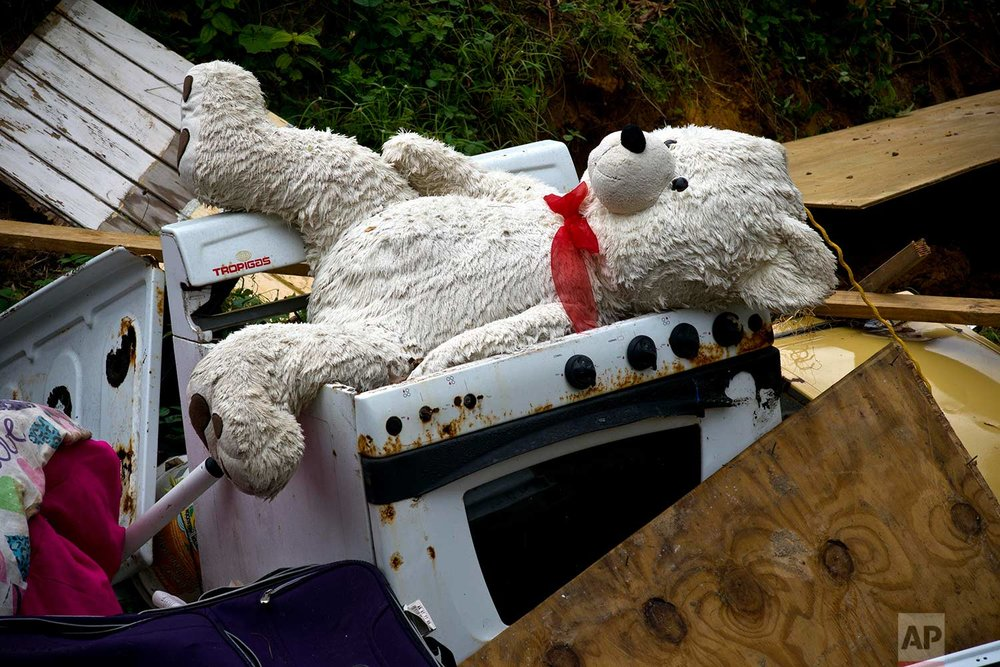 A teddy bear sits on the the belongings of the Sortre family, their home destroyed by Hurricane Maria, in the San Lorenzo neighborhood of Morovis, Puerto Rico, Saturday, Sept. 30, 2017. (AP Photo/Ramon Espinosa)