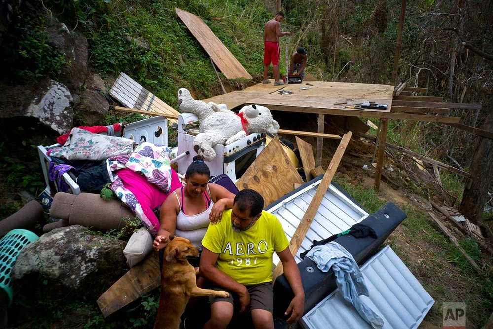 Yadira Sortre and William Fontan Quintero pose by what is left of their belongings, destroyed by Hurricane Maria while their children build a room to protect themselves from the elements, in the San Lorenzo neighborhood of Morovis, Puerto Rico, Saturday, Sept. 30, 2017. (AP Photo/Ramon Espinosa)