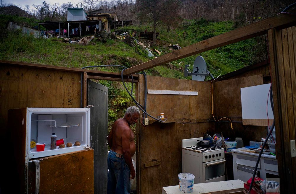 Angel Luis Sortre Vazquez walks into his sister's house destroyed by Hurricane Maria, in the San Lorenzo neighborhood of Morovis, Puerto Rico, Saturday, Sept. 30, 2017. (AP Photo/Ramon Espinosa)