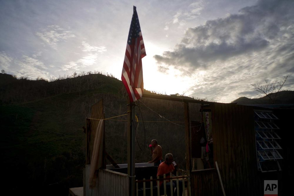 Ramon Sortre Vazquez, back, drinks coffee next to his brother Angel Luis, next to a flag of the United States in what is left of his house destroyed by Hurricane Maria, in Morovis, Puerto Rico, Sunday, Oct. 1, 2017. (AP Photo/Ramon Espinosa)