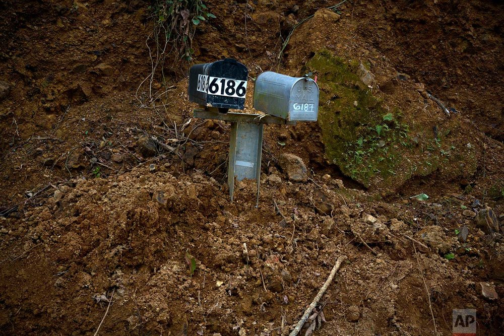 Two mailboxes are partially buried in mud because of a collapse caused by the rains of Hurricane Maria, in the San Lorenzo neighborhood of Morovis, Puerto Rico, Saturday, Sept. 30, 2017. (AP Photo/ Ramon Espinosa)