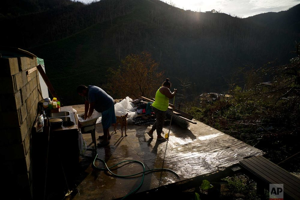 Yadira Sortre and William Fontan Quintero clean what is left of their house, destroyed by Hurricane Maria, in the San Lorenzo neighborhood of Morovis, Puerto Rico, Sunday, Oct. 1, 2017. (AP Photo/Ramon Espinosa)