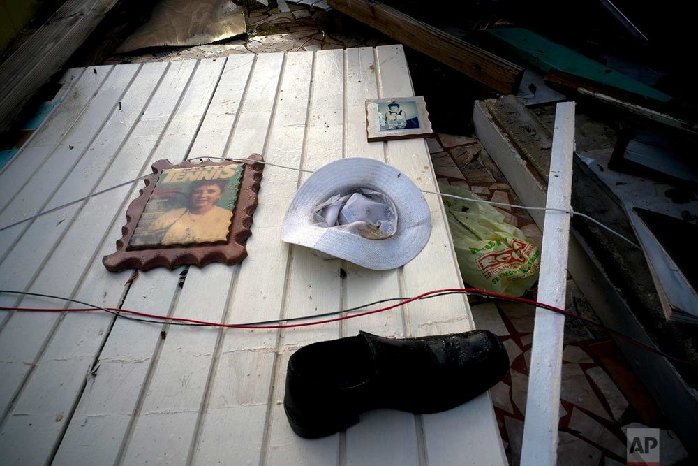 Two portraits, a hat and a shoe belonging to Luis Cosme litter a wall of his downed house destroyed by Hurricane Maria in the San Lorenzo neighborhood of Morovis, Puerto Rico, Sunday, Oct. 1, 2017. (AP Photo/Ramon Espinosa)