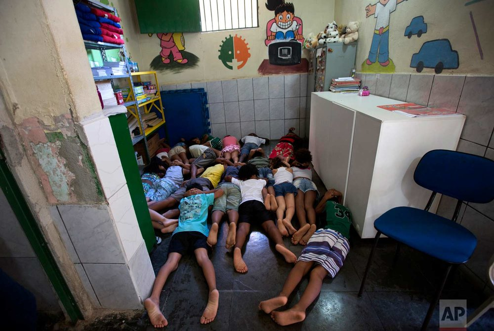 In this April 5, 2017 photo, students practice taking cover during shootings between gangsters and police, in a classroom at the Uere Special Needs School, in the Mare slum in Rio de Janeiro, Brazil. With rival drug dealers on practically every corner and a militarized campaign by authorities to take them out, shootouts have become so common that the school holds drills for students to practice taking cover quickly. (AP Photo/Silvia Izquierdo)