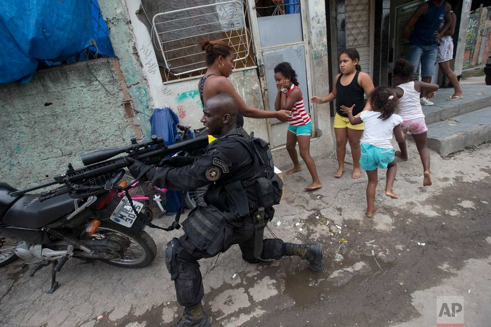 "In this March 26, 2014 photo, an officer with the Special Police Operations Battalion takes position while residents run for cover during an operation in the Mare slum complex, ahead of its ""pacification"" security program, in Rio de Janeiro, Brazil. At the time the city had two global showcase events on the horizon that were incentives to make the program work: the 2014 World Cup in Brazil and the 2016 Rio Summer Olympics. (AP Photo/Silvia Izquierdo)"