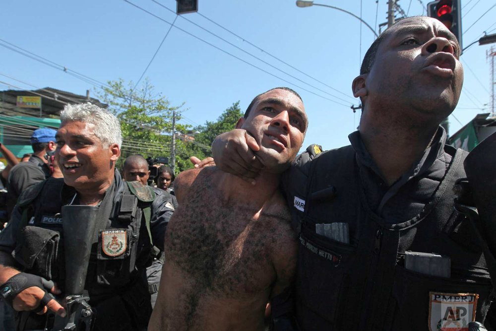 In this Nov. 28, 2010 photo, Zeu, an alleged drug trafficker, is detained during a police operation at the Alemao complex of slums, in Rio de Janeiro, Brazil. In late November 2010, security forces seized control of what many believe to be the city's most dangerous slum, claiming victory in the ongoing battle against drug gangs. The victory appears to have been temporary. (AP Photo/Silvia Izquierdo)