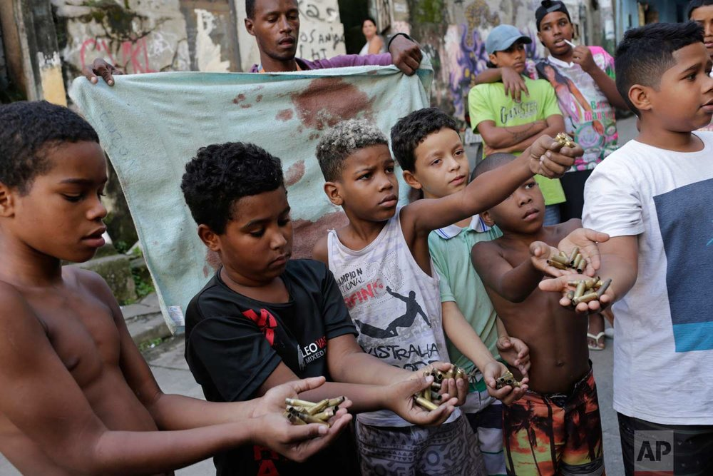 In this June 30, 2017 photo, children show spent bullet casings, backdropped by a blood-stained towel, after a shootout between police and drug traffickers at the Mangueira slum, in Rio de Janeiro, Brazil. The towel is stained with the blood of a 76-year-old woman and her daughter, both killed in the crossfire of a police operation. Marlene Maria da Conceicao was shot in the neck in the doorway of her home and her 42-year-old daughter, Ana Cristina was hit when she tried to help her mother. (AP Photo/Silvia Izquierdo)