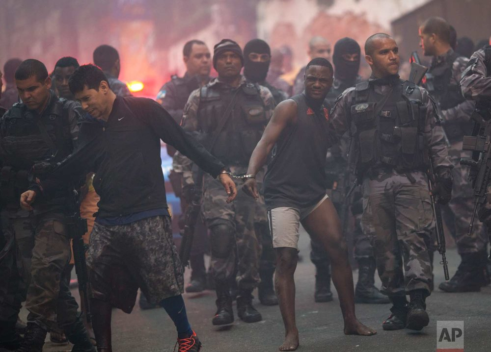 In this Oct. 10, 2016 photo, police escort men detained during an operation in the Pavao Pavaozinho slum in Rio de Janeiro, Brazil. An hours-long shootout between police and suspected criminals left three people dead, as well as blocking streets and closing shops in the posh Copacabana and Ipanema districts. The slum is entrenched between and overlooks the two fancy neighborhoods. (AP Photo/Silvia Izquierdo)
