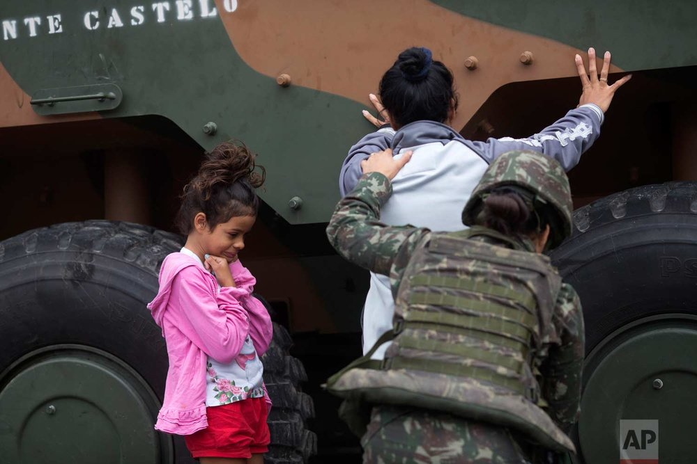 In this Aug. 21, 2017 photo, a soldier pats down a woman as a girl waits during a security operation at the Jacarezinho slum, in Rio de Janeiro, Brazil. In July the federal government deployed over 8,500 troops to try to stamp out crime in Rio's roughest neighborhoods. But so far they have not been able to stem the bloodshed. (AP Photo/Silvia Izquierdo)