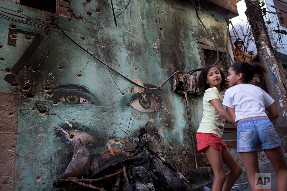 In this Sept. 27, 2017 photo, girls walk past a wall riddled with bullet holes from shootings between rival drug traffickers, at the Rocinha slum, in Rio de Janeiro, Brazil. Violence is on the rise in Rio's slums after several years of decline, and the killings of kids have shocked even residents long inured to deaths from gangs and police. (AP Photo/Silvia Izquierdo)