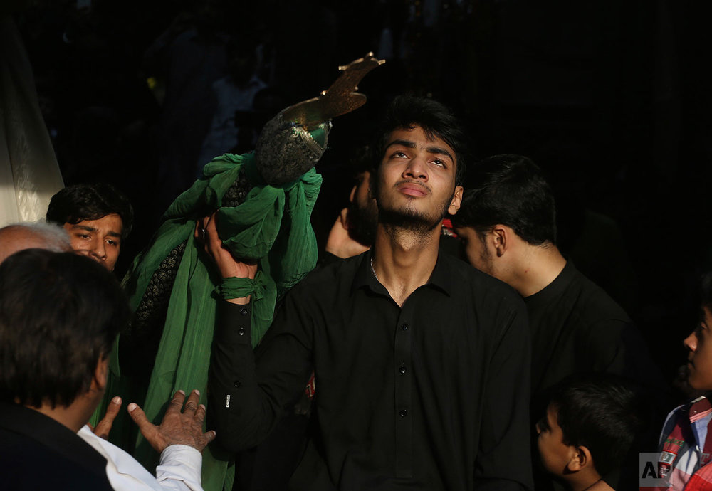 Pakistani Shiite Muslims participate in a Muharram procession in Peshawar, Pakistan, Thursday, Sept. 28, 2017. Muharram is a month of mourning in remembrance of the martyrdom of Imam Hussein, the grandson of Prophet Mohammed. (AP Photo/Muhammad Sajjad)