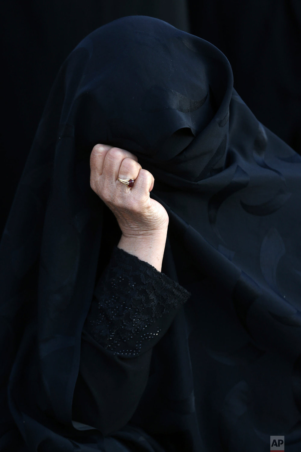 An elderly woman takes part in a procession during the Muslim month of Muharram, an important period of mourning for Muslim Shiites which marks the anniversary of martyrdom of Imam Hussein, a grandson of Prophet Muhammad and the third Shiite saint, who was killed during a battle in Karbala in present-day Iraq in 7th century, in Tehran, Iran, Friday, Sept. 29, 2017. (AP Photo/Vahid Salemi)