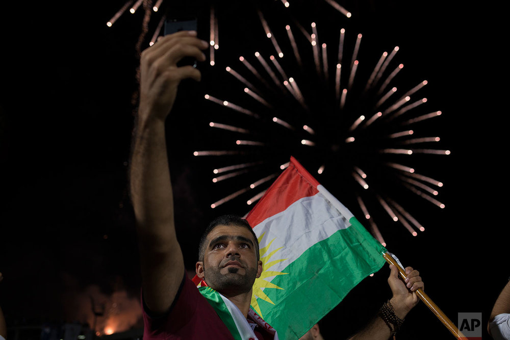 A man takes a selfie in front of a fireworks display at a pro independence rally in Irbil, Friday, Sept. 22, 2017. (AP Photo/Bram Janssen)