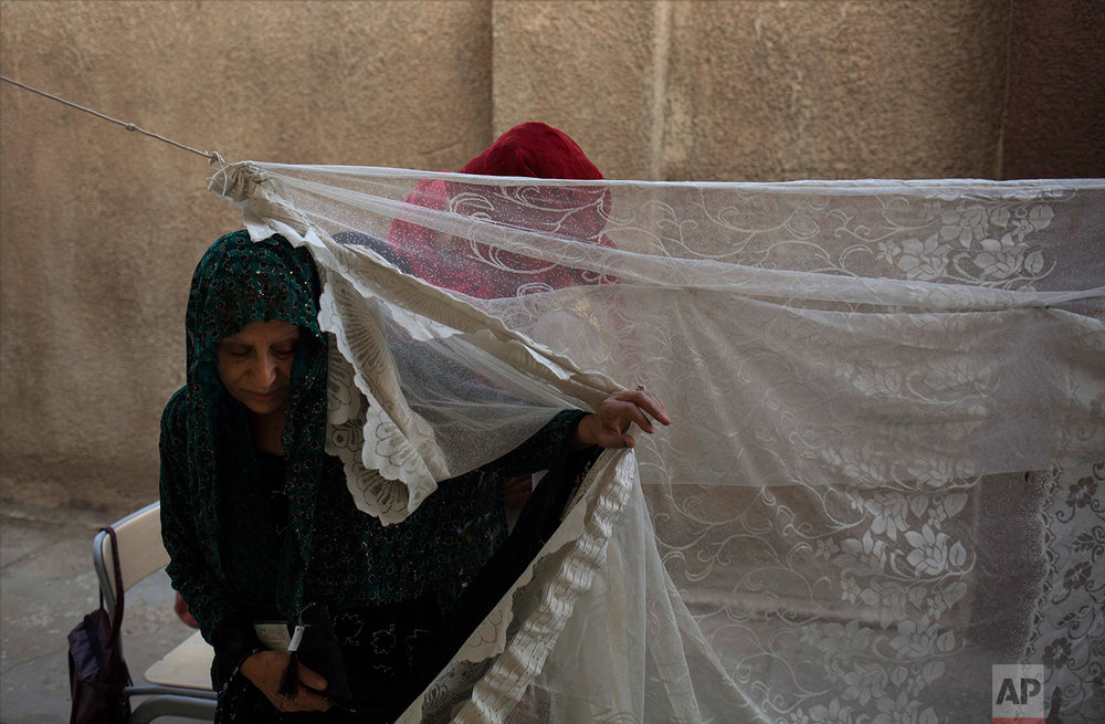 A woman leaves a security checkpoint for women before entering a polling station in the disputed city of Kirkuk, Monday, Sept. 25, 2017. (AP Photo/Bram Janssen)