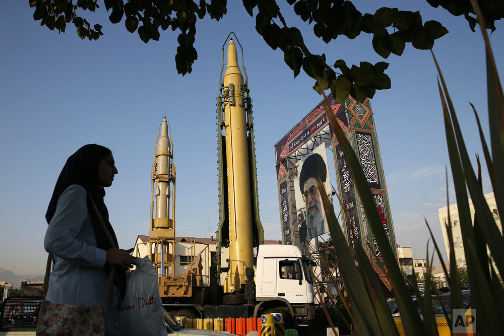 A Ghadr-H missle, center, a solid-fuel surface-to-surface Sejjil missile and a portrait of the Supreme Leader Ayatollah Ali Khamenei are on display for the annual Defense Week, marking the 37th anniversary of the 1980s Iran-Iraq war, at Baharestan Sq. in Tehran, Iran, Sunday, Sept. 24, 2017. (AP Photo/Vahid Salemi)