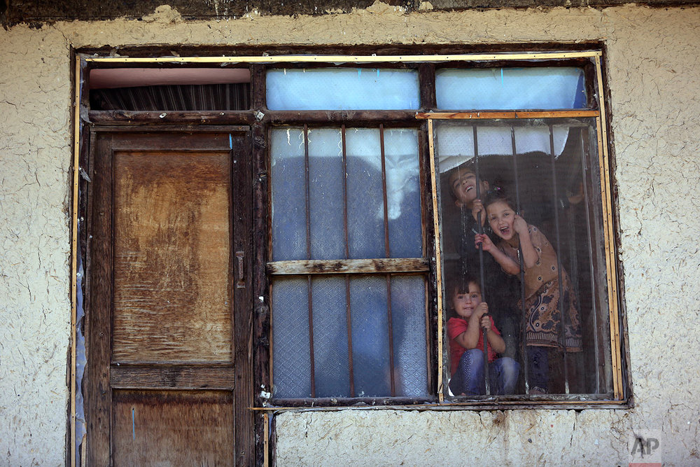 Afghan children look outside through the window of their home as they poses for photograph in the old part of Kabul, Afghanistan, Tuesday, Sept. 26, 2017. (AP Photo/Rahmat Gul)