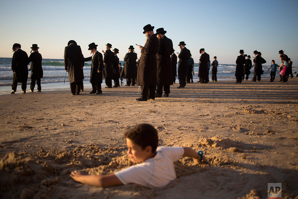 A boy is covered in sand as ultra-Orthodox Jewish men of the Vizhnitz Hassidic sect pray on a hill overlooking the Mediterranean Sea as they participate in a Tashlich ceremony, in Herzeliya, Israel, Thursday, Sept. 28, 2017. (AP Photo/Ariel Schalit)