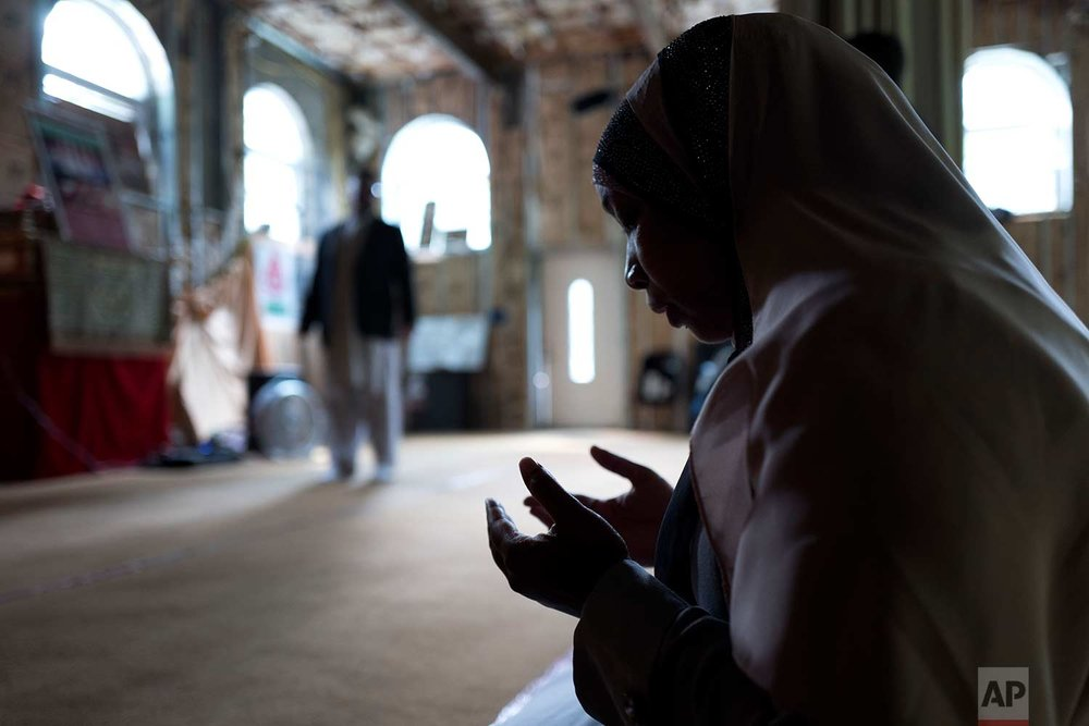 In this Sept. 7, 2017 photo, Tahirah Clark, an attorney for the Muslim enclave of Islamberg, prays in the community's mosque in Tompkins, N.Y. (AP Photo/Mark Lennihan)