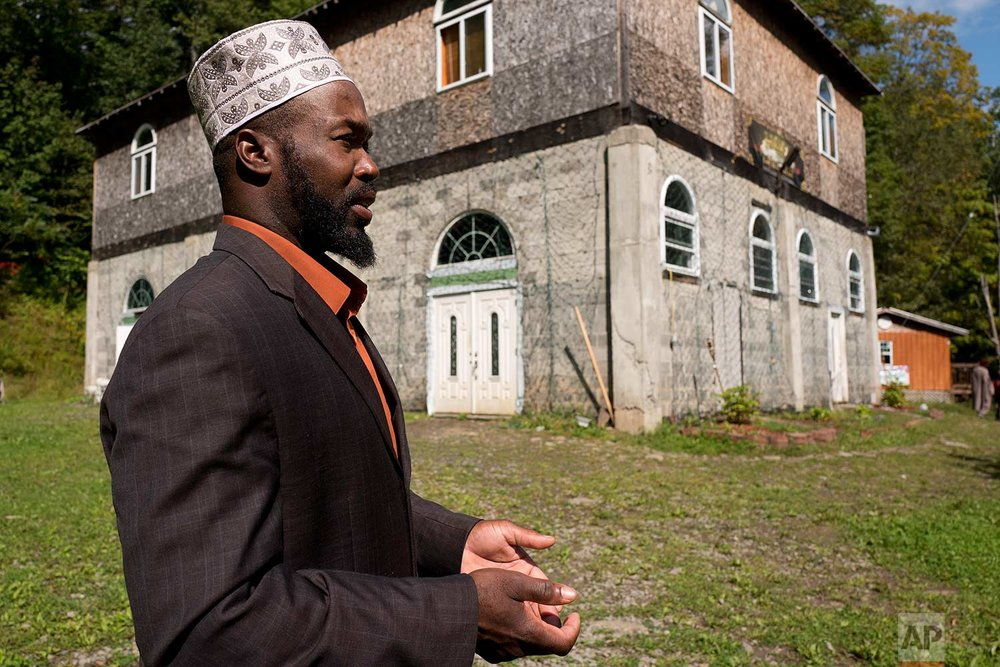 In this Sept. 7, 2017 photo, Rashid Clark discusses his Muslim community while standing outside the enclave's mosque in Tompkins, N.Y. (AP Photo/Mark Lennihan)