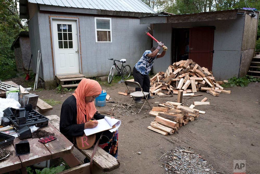 In this Sept. 7, 2017 photo, a girl studies for school while a man chops wood in the Muslim enclave of Islamberg in Tompkins, N.Y. (AP Photo/Mark Lennihan)