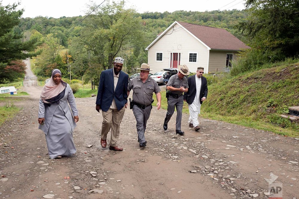 In this Sept. 7, 2017 photo, Tahirah Clark, left, and Faruq Baqi walk with New York State Police Capt. Scott Heggelke, center, in the Muslim enclave of Islamberg in Tompkins, N.Y. With them are Maj. James Barnes, second from right, and Muhammad Matthew Gardner, right, a spokesman for The Muslims of America. (AP Photo/Mark Lennihan)