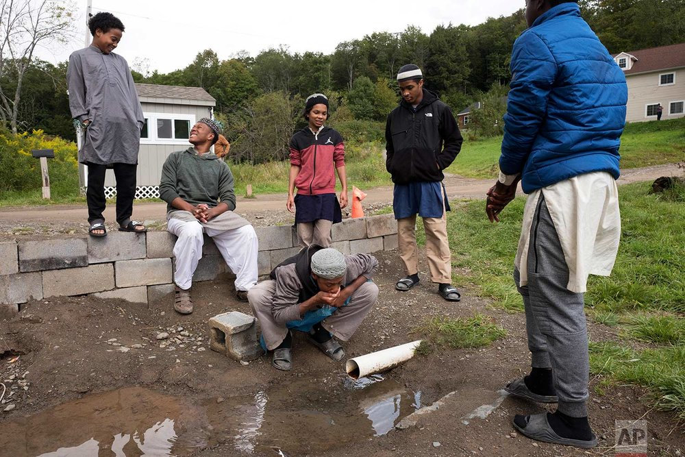 In this Sept. 7, 2017 photo, Muslim schoolboys stop to drink from a pipe carrying well water at Islamberg in Tompkins, N.Y. People in the Muslim enclave of Islamberg in upstate New York say they are frustrated by repeated accusations that their community is a breeding ground for terror. Though police and analysts dismiss those accusations, they have persisted from the time the enclave was settled near the Catskill Mountains in the 1980s. (AP Photo/Mark Lennihan)