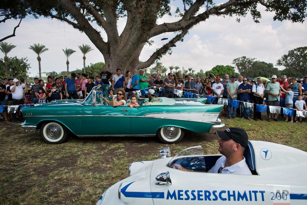 "Spectators looks at 1957 Chevy Bel Air and 1957 Messerschmitt during the 31st annual ""Five Club"" car collectors' meeting in Ramat Gan, Israel, Friday, Oct. 6, 2017. (AP Photo/Oded Balilty)"