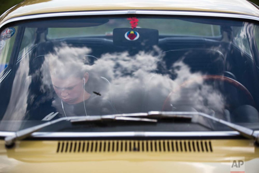 "A youth sits in his grandfather antique car during the 31st annual ""Five Club"" car collectors' meeting in Ramat Gan, Israel, Friday, Oct. 6, 2017. (AP Photo/Oded Balilty)"