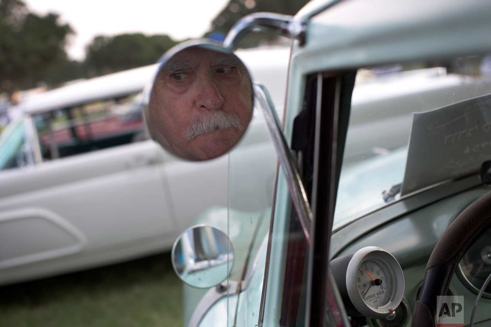 "Zelig Rabinowitz reflected in his 1956 Dodge Coronet mirror during the 31st annual ""Five Club"" car collectors' meeting in Ramat Gan, Israel, Friday, Oct. 6, 2017. (AP Photo/Oded Balilty)"