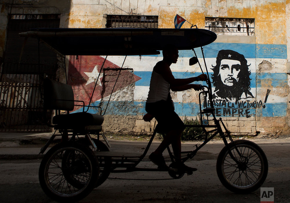"A bicycle taxi rides past a building painted with a Cuban flag and an image of Che Guevara, along with the Spanish slogan ""Always toward victory!"" in Havana, Cuba, Saturday, March 19, 2016. (AP Photo/Rebecca Blackwell)"