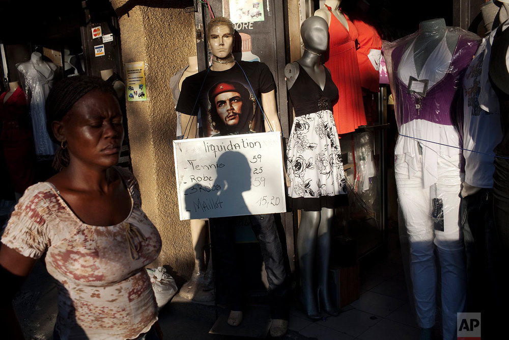 "A woman walks past a dummy wearing a t-shirt of Cuban revolutionary Ernesto ""Che"" Guevara at the Petion Ville neighborhood in Port-au-Prince, Haiti, Thursday, Feb. 3, 2011. (AP Photo/Rodrigo Abd)"