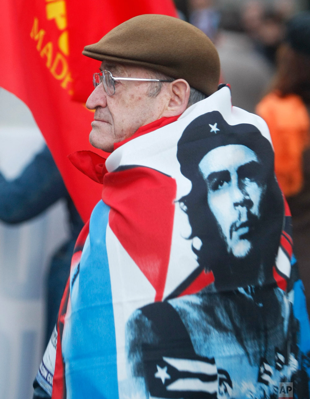 A demonstrator draped with a flag showing the face of Che Guevara, the legendary guerrilla and revolutionary icon, marches in Madrid Saturday Jan. 31, 2009  to mark the the 50th Anniversary of the Cuban Revolution. (AP Photo/Paul White)