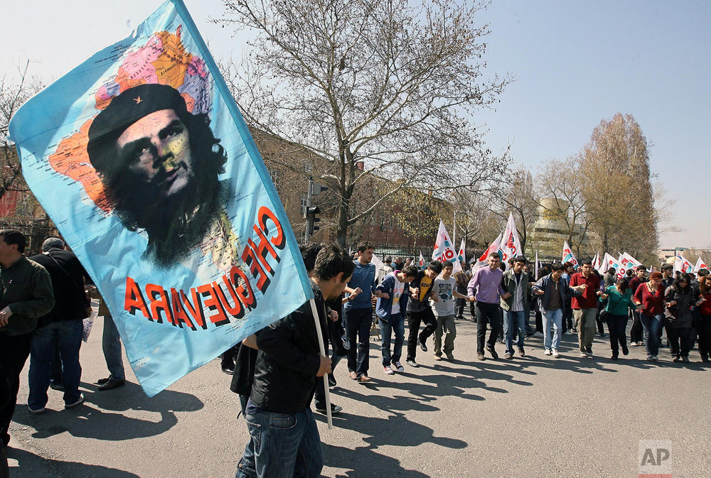Turkish students demonstrate as one of them waves a flag with a poster of Latin American revolutionary legend Che Guevara during a protest rally against NATO and U. S. President Barack Obama, in Ankara, Turkey, Saturday, April 4, 2009. (AP Photo/Burhan Ozbilici)