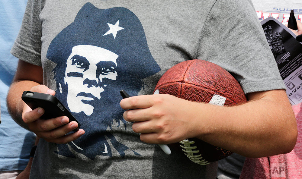 A New England Patriots fan, wearing a Che Guevara-like t-shirt depicting quarterback Tom Brady, waits for a chance to get an autograph during an NFL football training camp in Foxborough, Mass., Thursday, July 30, 2015. (AP Photo/Charles Krupa)
