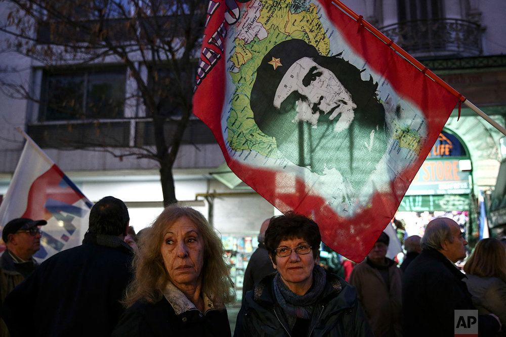 Supporters of the communist-affiliated union PAME stand beneath a flag depicting Cuban revolutionary leader Che Guevara during an anti-austerity rally in Athens, Tuesday, Feb. 21, 2017. (AP Photo/Yorgos Karahalis)