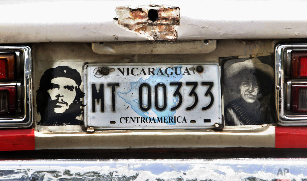 "A car decorated with images of Argentinian revolutionary leader Ernesto ""Che"" Guevara, left, and Nicaragua's national hero Augusto C. Sandino, right, is seen in Managua, Tuesday, June 26, 2007. (AP Photo/Esteban Felix)"
