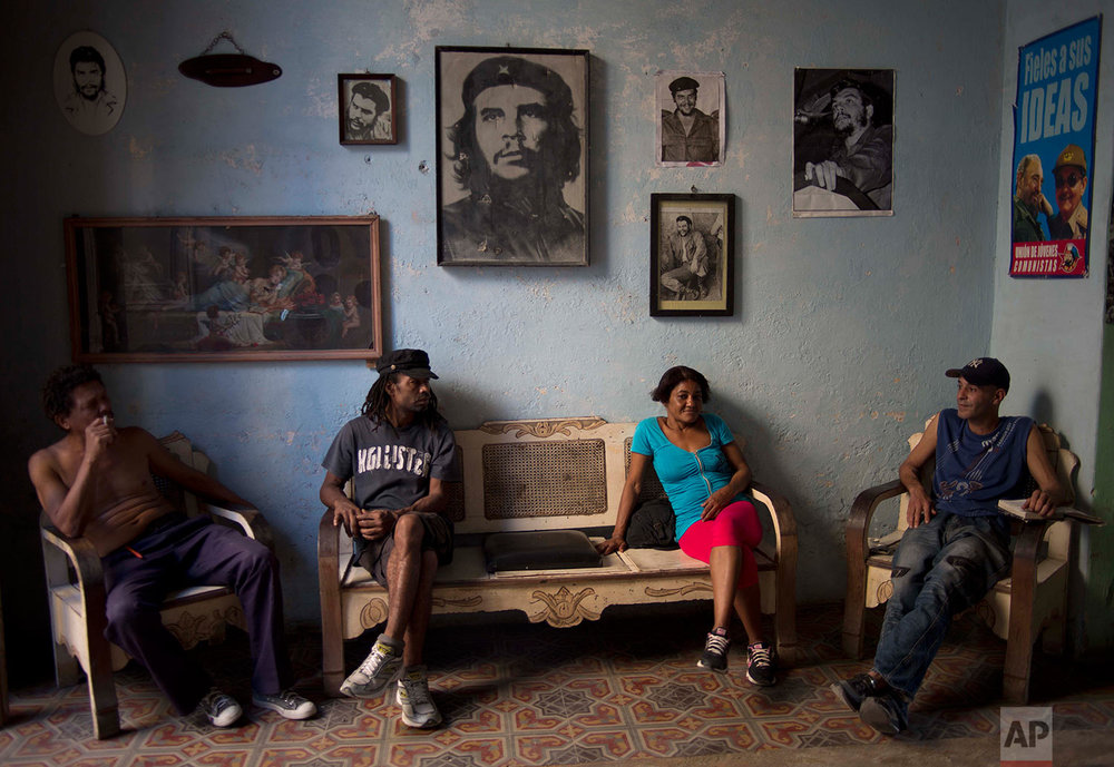 Roberto Alvarez, 47, right, chats with friends backdropped by a wall decorated with images of Cuban revolutionary heroes, Che Guevara, Fidel Castro and his brother, President Raul Castro, in Havana, Cuba, Wednesday, Feb. 25, 2015. (AP Photo/Ramon Espinosa)