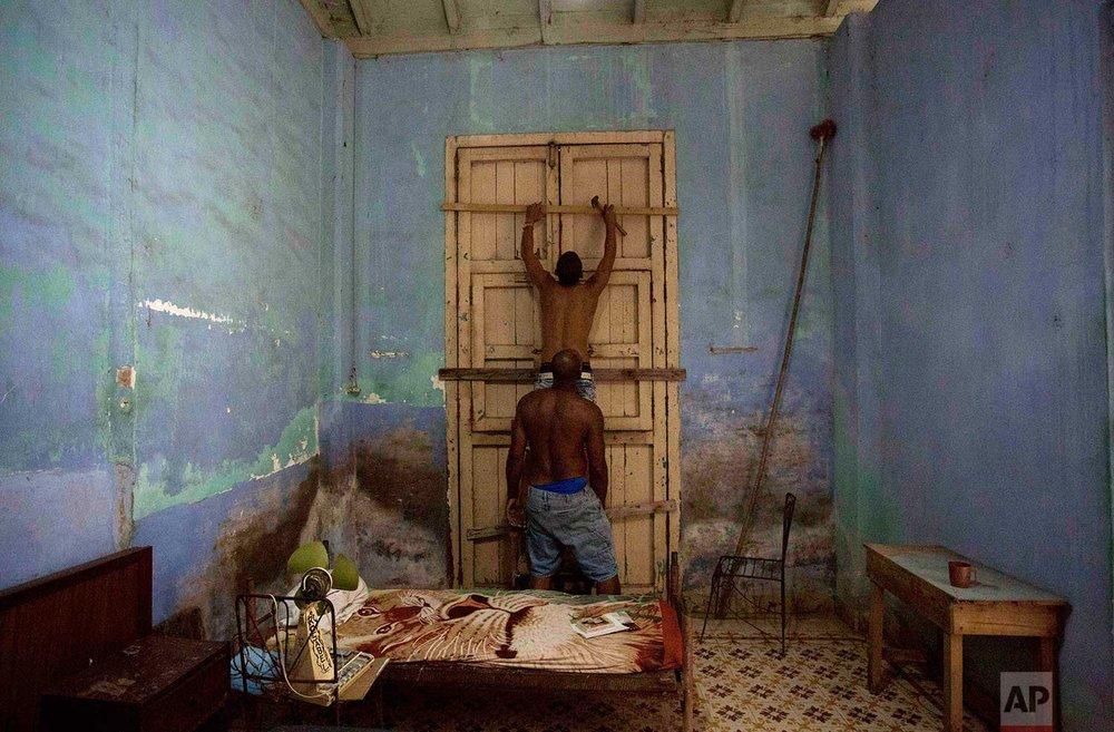 Men board up a door in preparation for Hurricane Irma in Caibarien, Cuba, Friday, Sept. 8, 2017. (AP Photo/Desmond Boylan)