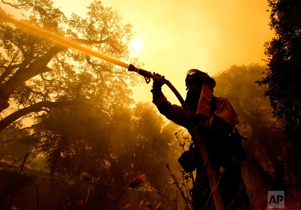 Napa County firefighter Jason Sheumann sprays water on a home as he battles flames from a wildfire Monday, Oct. 9, 2017, in Napa, Calif. (AP Photo/Rich Pedroncelli)
