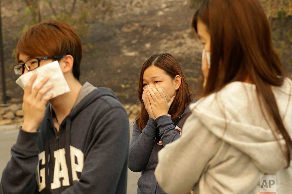 Vincent Yeoh, from left, Ai Peng, Estella Fong, all from Malaysia, cover their mouths from smoke coming from a burning Hilton Sonoma Wine Country hotel, where they were all staying, in Santa Rosa, Calif., Monday, Oct. 9, 2017. (AP Photo/Jeff Chiu)