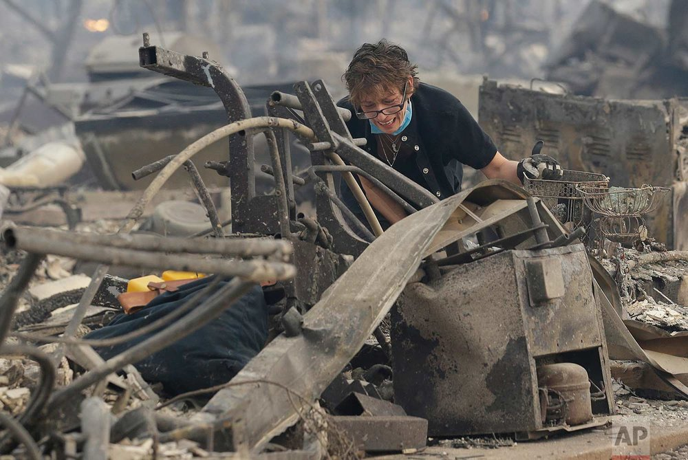 Kristine Pond reacts as she searches the remains of her family's home destroyed by fires in Santa Rosa, Calif., Monday, Oct. 9, 2017. (AP Photo/Jeff Chiu)