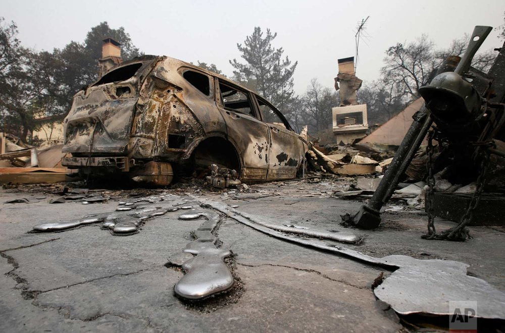 Rivers of melted metal flow from a vehicle parked at a home, Tuesday, Oct. 10, 2017, that was destroyed by a wildfire near Napa, Calif.  (AP Photo/Rich Pedroncelli)