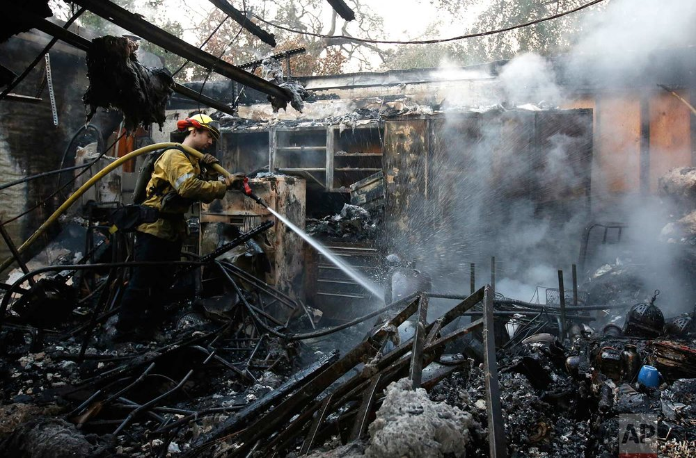 Firefighter Nick Gonzalez-Pomo, of the San Rafael Fire Department, waters down smoldering ashes on a garage Tuesday, Oct. 10, 2017, in Napa, Calif. (AP Photo/Rich Pedroncelli)