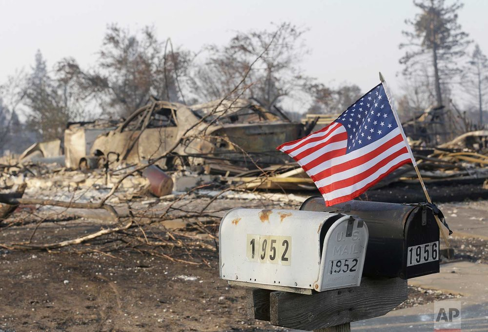 A small flag attached to mailboxes flies in front of homes destroyed by fires in Santa Rosa, Calif., Wednesday, Oct. 11, 2017. (AP Photo/Jeff Chiu)