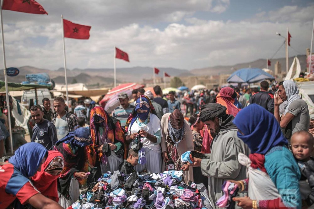 In this Friday, Sept. 22, 2017 photo, Berber villagers shop for garments at the annual festival of Imilchil, a small village in Morocco's Atlas mountains. (AP Photo/Mosa'ab Elshamy)