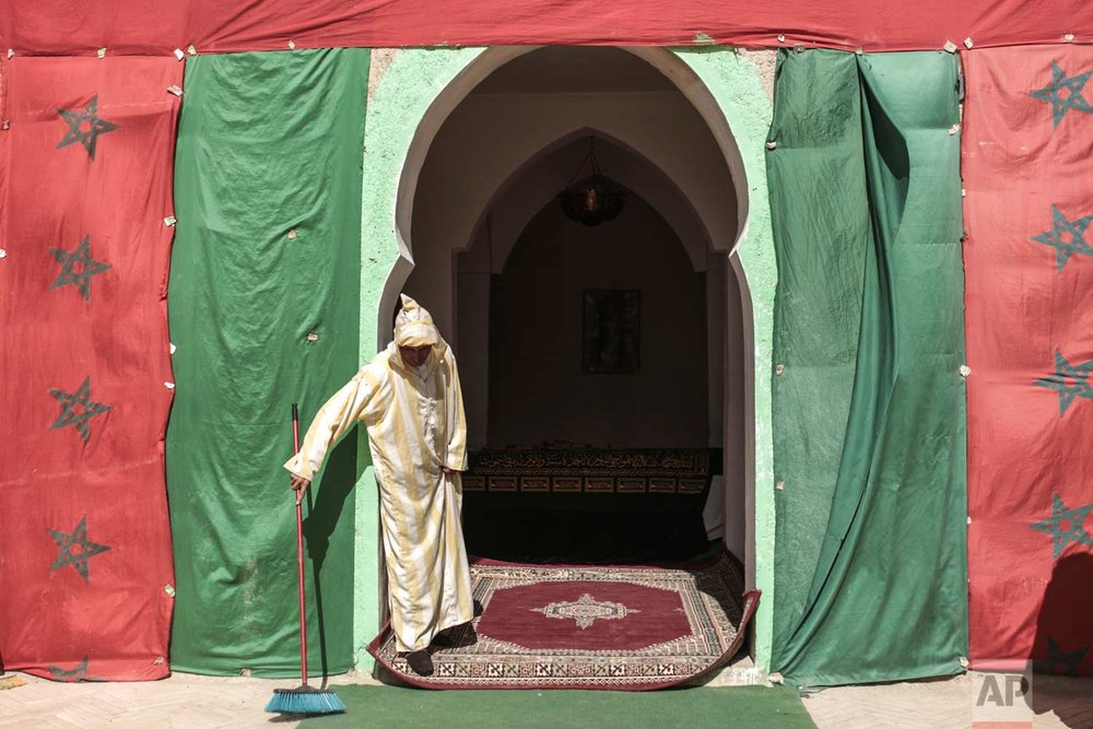 In this Saturday, Sept. 23, 2017 photo, a caretaker cleans outside the mausoleum of Sidi Hmad Mghani, a local saint, at the annual festival of Imilchil, a small village in Morocco's Atlas mountains. (AP Photo/Mosa'ab Elshamy)
