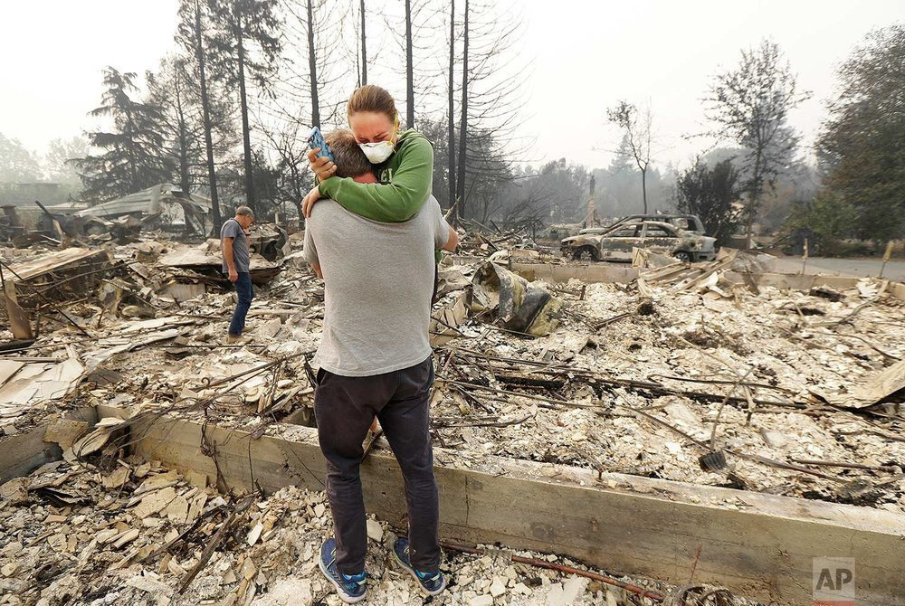 Todd Caughey hugs his daughter, Ella, on Tuesday, Oct. 10, 2017, as they visit the site of their home destroyed by fires in Kenwood, Calif. (AP Photo/Jeff Chiu)